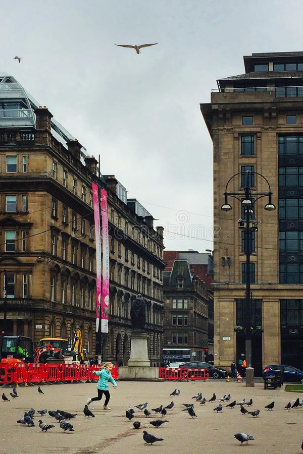 Девушка гоня голубей в городской площади стоковая фотография rf
