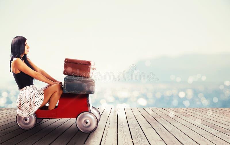 Девушка готовая для того чтобы путешествовать с малым автомобилем полным багажей стоковые изображения
