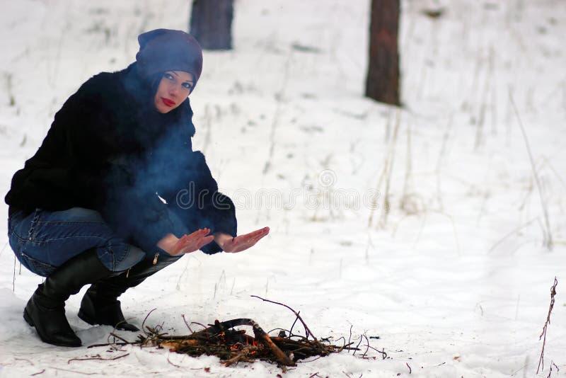 Download Девушка греет его руки над огнем в зиме Стоковое Фото - изображение: 50252299