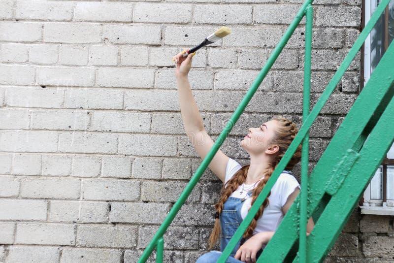 Девушка делает подготовку для красить деревянное поверхностное газебо, загородку стоковые изображения rf