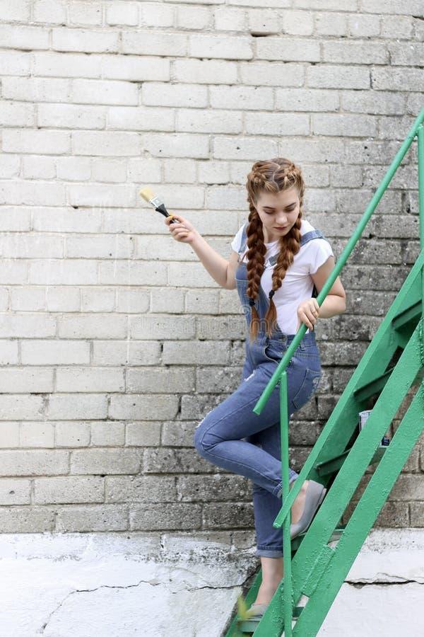 Девушка делает подготовку для красить деревянное поверхностное газебо, загородку стоковая фотография rf