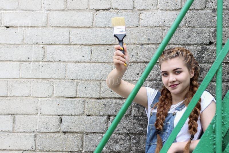 Девушка делает подготовку для красить деревянное поверхностное газебо, загородку стоковые фотографии rf
