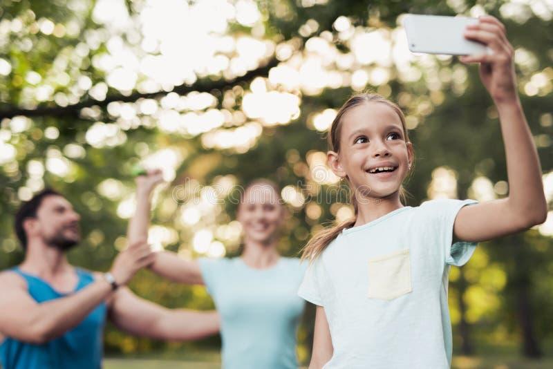 Девушка делает selfie в парке с ее семьей Представлять матери и отца на фоне стоковая фотография rf