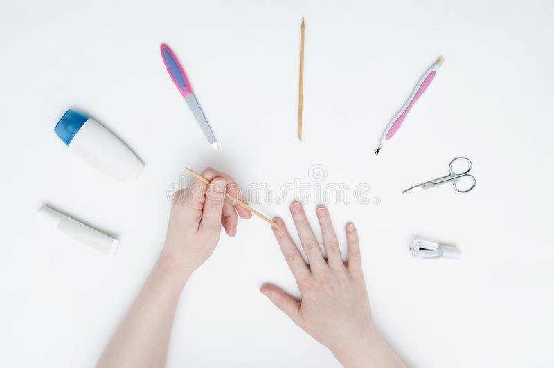 Девушка делая маникюр на белой таблице стоковые фотографии rf