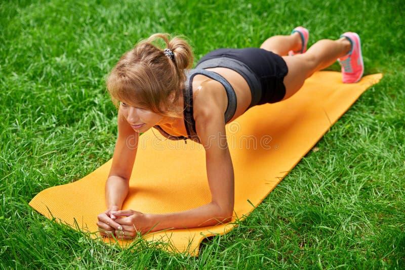Девушка делая тренировки на циновке в парке на зеленой траве стоковые фото