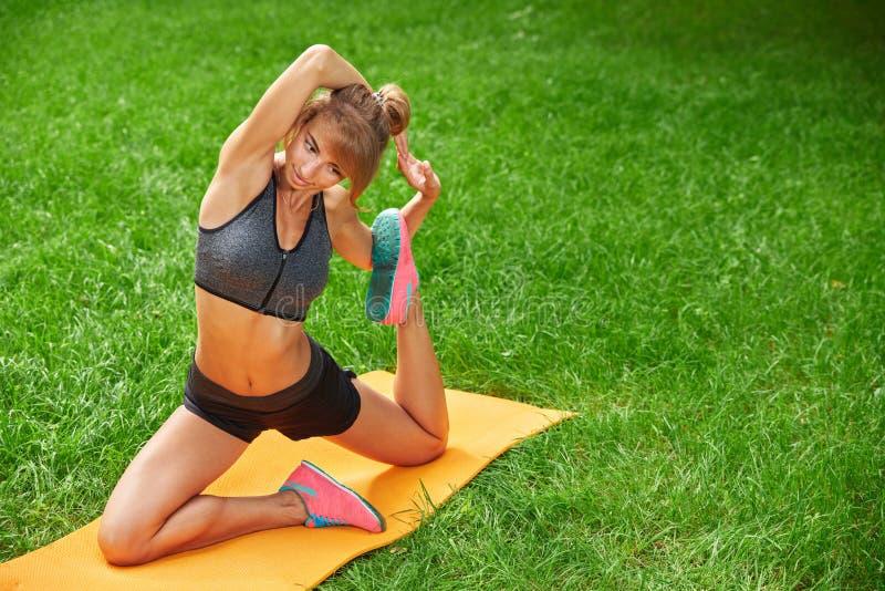 Девушка делая тренировки на циновке в парке на зеленой траве стоковое фото