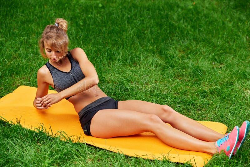 Девушка делая тренировки на циновке в парке на зеленой траве стоковое изображение