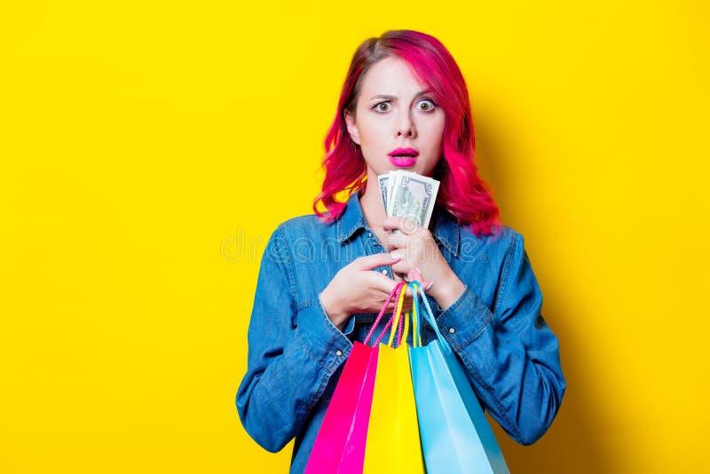 Девушка держащ покрашенные хозяйственные сумки и деньги стоковые изображения rf