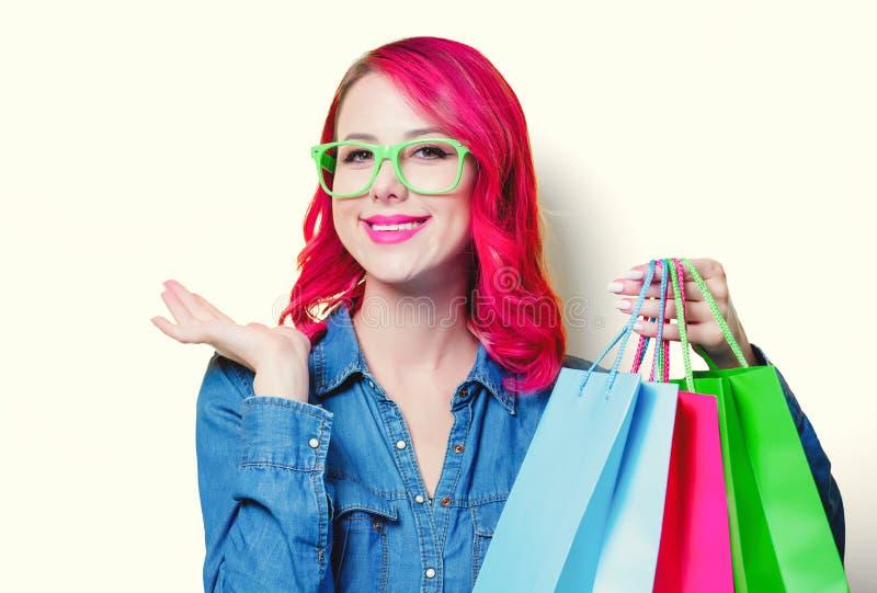 Девушка держащ покрашенные хозяйственные сумки стоковое изображение