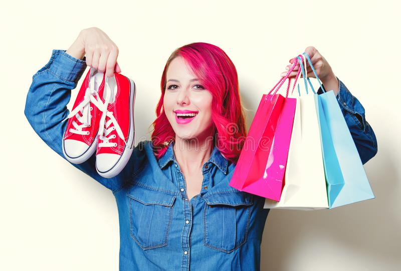 Девушка держащ хозяйственные сумки и красные gumshoes стоковое фото