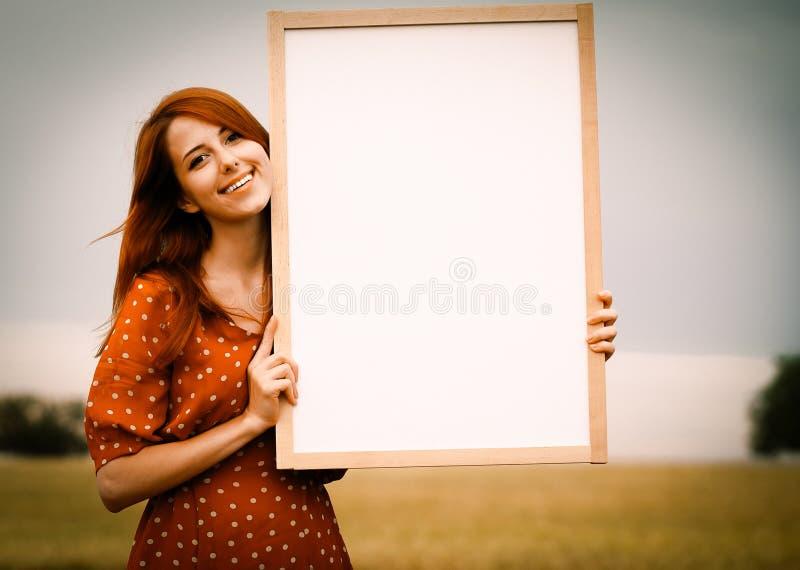 Девушка держа белую доску в ее руках на поле стоковые фотографии rf