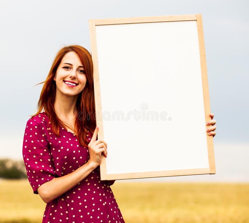 Девушка держа белую доску в ее руках на поле стоковые изображения rf