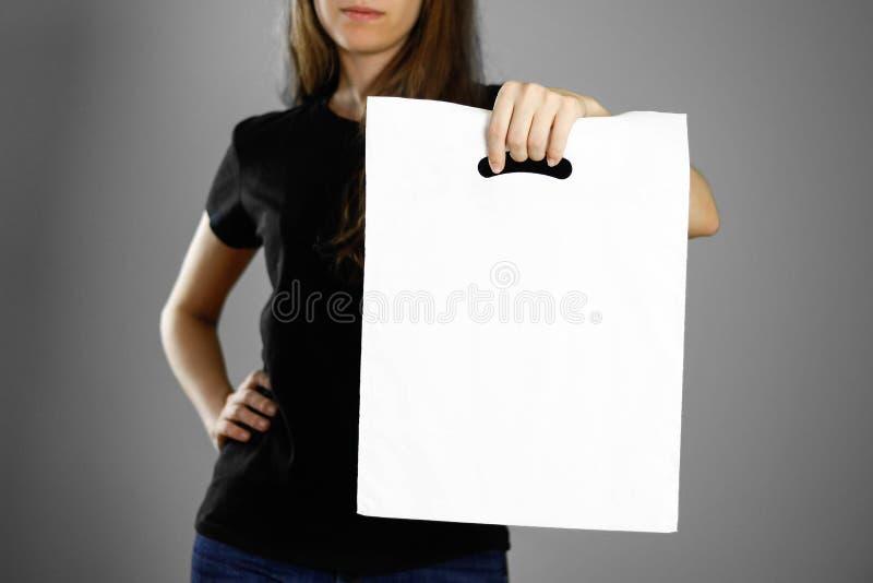 Девушка держа белый полиэтиленовый пакет конец вверх Изолированная предпосылка стоковое фото rf