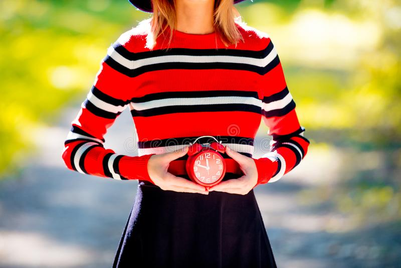 Девушка держа будильник в парке стоковые изображения rf