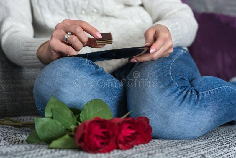 Девушка держа конфету и плиту шоколада в руках на коленях и красных розах стоковые изображения