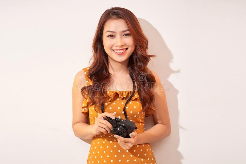 Девушка держа ретро камеру Модельный представлять на бежевой предпосылке в шляпе стоковые изображения rf