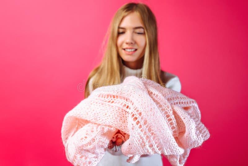 Девушка держа розовый теплый шарф на красной предпосылке стоковое фото rf