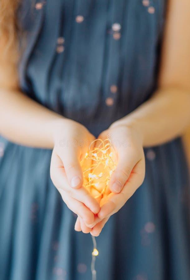 девушка держа свет декоративных ладоней гирлянды теплый стоковые изображения rf