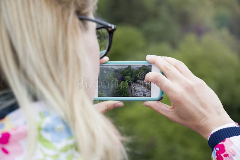 Девушка держа телефон для того чтобы сфотографировать взгляд ландшафта стоковое фото rf