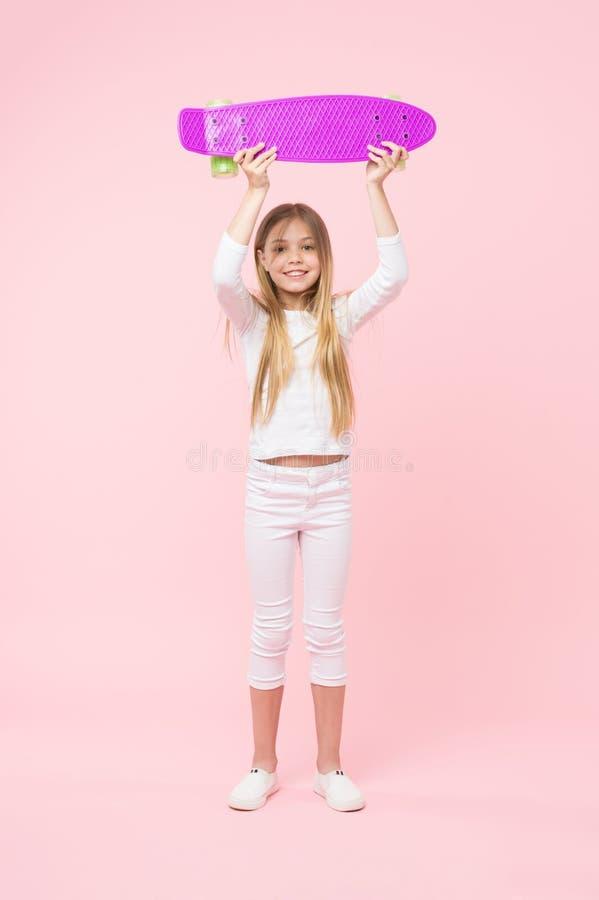 Девушка держа фиолетовый скейтборд над ее головой Чемпион в гонке улицы, счастливой концепции детства Ребенк в белом шлямбуре стоковые изображения