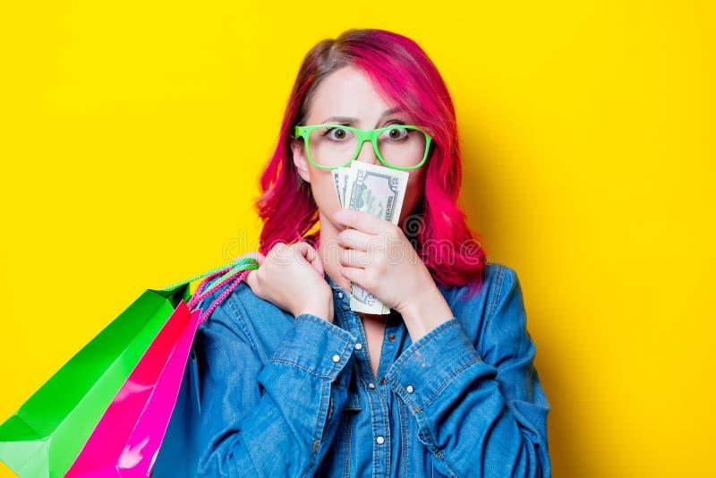 Девушка держа хозяйственные сумки с деньгами стоковые фото