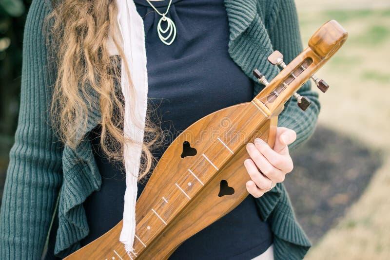 Девушка держа Dulcimer горы стоковые фото
