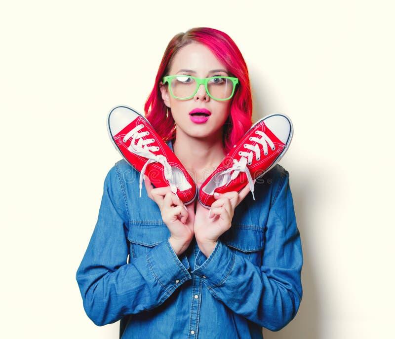 Девушка держа gumshoes красного цвета желаний стоковое фото rf