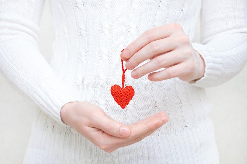 Девушка держит в ее руке красное сердце связанное шерстей стоковые изображения rf