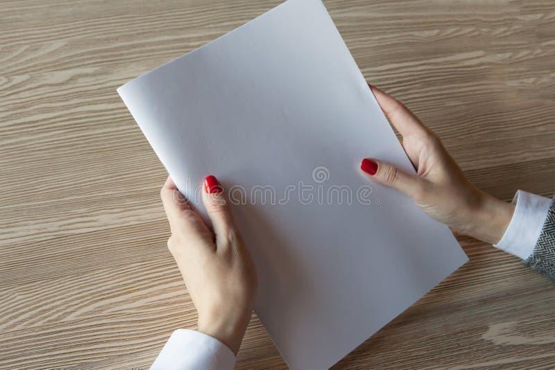 Девушка держит в руке модель журнала формат A4 стоковые фотографии rf