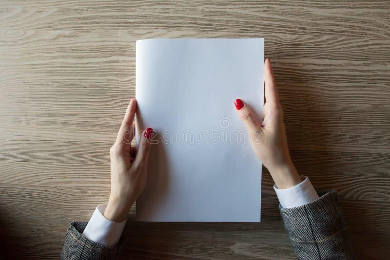 Девушка держит в руке модель журнала формат A4 стоковое изображение rf