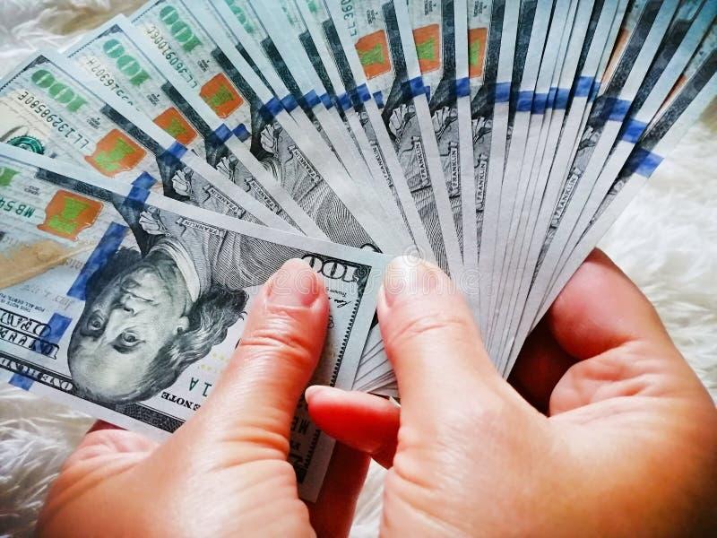 Девушка держит деньги в ее руках 100 долларов наличных денег бесплатная иллюстрация