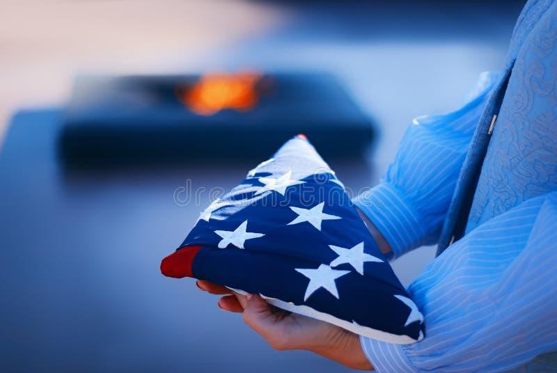 Счастливый День памяти погибших в войнах Девушка держит сложенный американский флаг в ее руках, между пылая огнем памяти Концепци стоковые фотографии rf