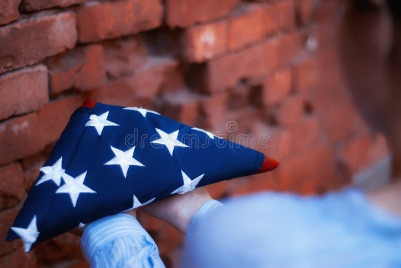 Счастливый День памяти погибших в войнах Девушка держит сложенный американский флаг в ее руках, против кирпичной стены стоковая фотография