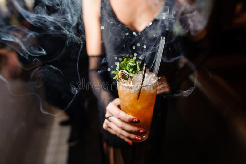 Девушка держит спиртной оранжевый коктеиль с льдом и хворостиной сухой и свежей мяты стоковое фото rf