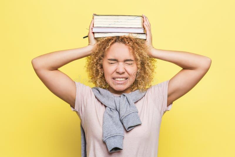 Девушка держит тяжелые книги на ее руках Тягостно Она страдает Изолировано на желтой предпосылке стоковые фотографии rf