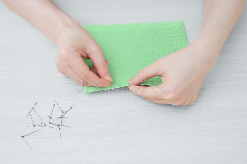 Девушка держит часть зеленой ткани и иглы для того чтобы сшить ткань стоковые фото