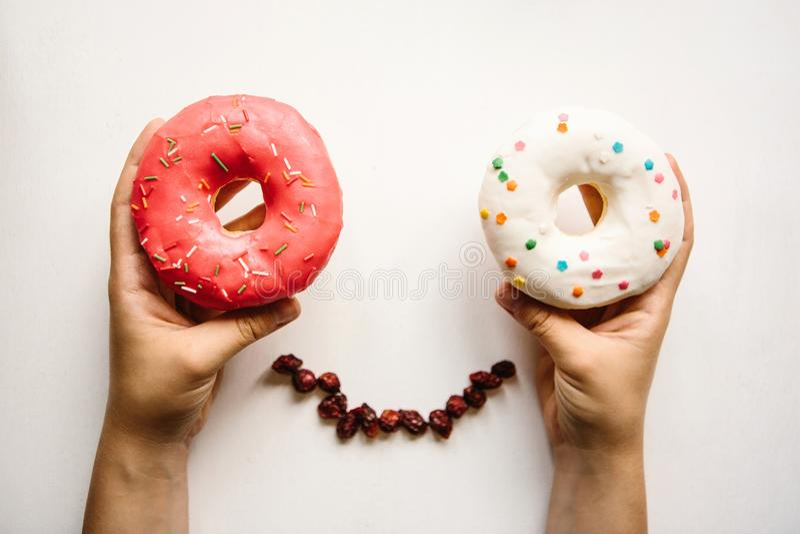 Девушка держит donuts в ее руках на белой предпосылке Оно выглядеть как положительная персона с глазами от donuts стоковые фотографии rf