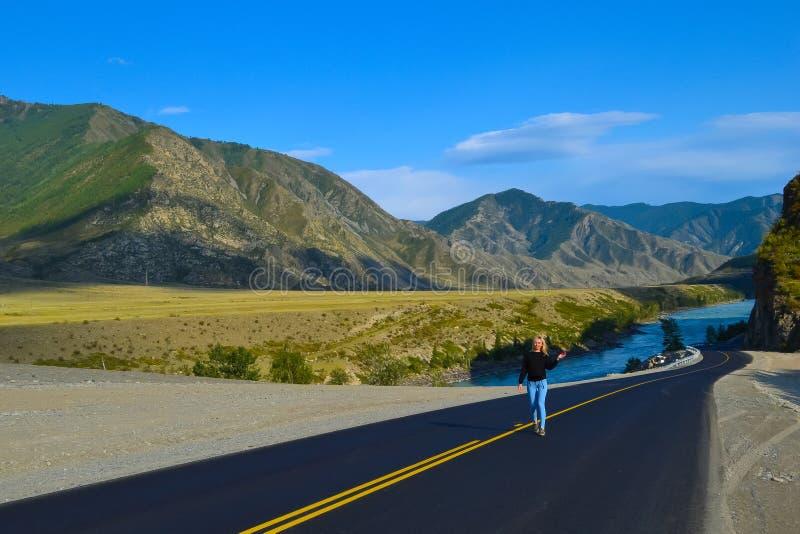 Девушка детенышей довольно белокурая на черной дороге асфальта с желтым mar стоковая фотография