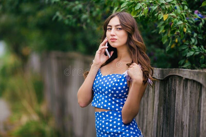 Девушка детенышей довольно ультрамодная усмехаясь говоря на умном телефоне в c стоковое фото