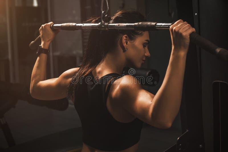 Девушка детенышей подходящая атлетическая имея разминку в спортзале Тренировка брюнета красивая здоровая женская крытая стоковые фото