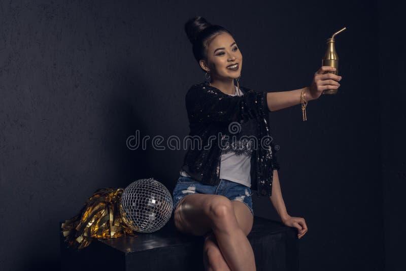 девушка диско очарования азиатская с золотыми шариком и pom-pom диско бутылки стоковое фото