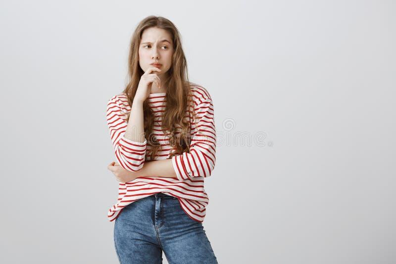 Девушка думает как прыгнуть классы Портрет очаровательного белокурого подростка в милом striped свитере держа руку на подбородке стоковые фото