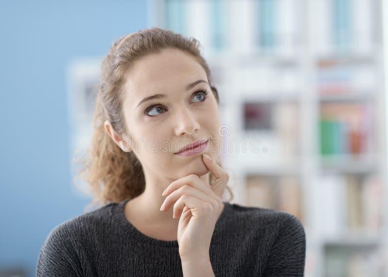 Девушка думая с рукой на подбородке стоковое изображение