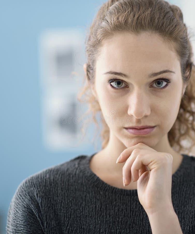 Девушка думая с рукой на подбородке стоковая фотография