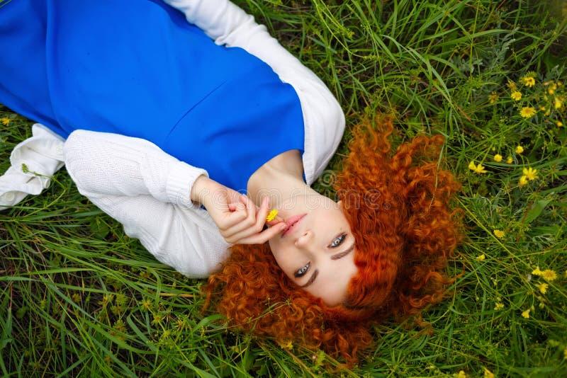 Девушка лежа в луге окруженном цветками стоковое фото rf
