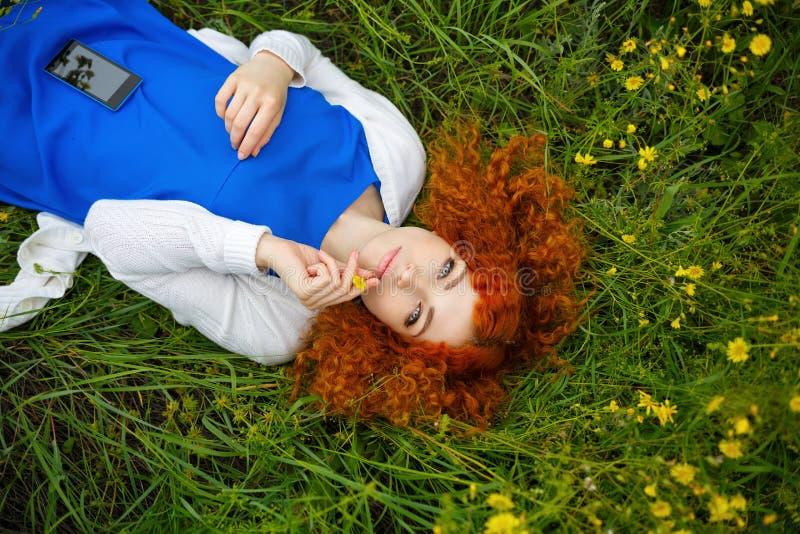 Девушка лежа в луге среди цветков стоковая фотография rf