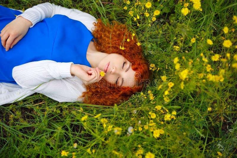 Девушка лежа в луге среди цветков стоковое изображение