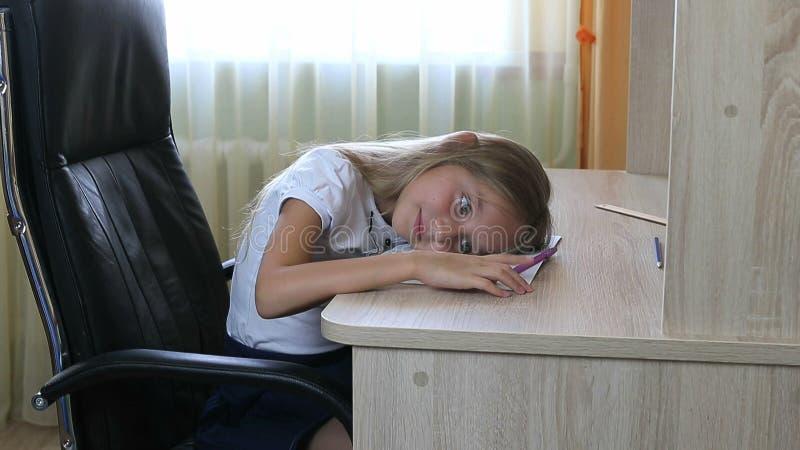 Девушка лежа на таблице Исследование утомлянное маленькой девочкой Кавказская девушка лежа вниз Унылая съемка крупного плана стор стоковое фото