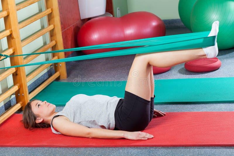 Девушка лежа на циновке тренировки и протягивая ноги стоковые изображения rf