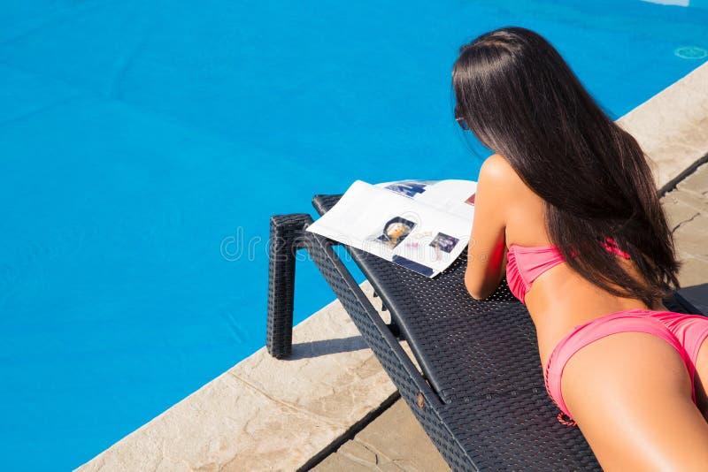 Девушка лежа на deckchair и читая кассету стоковые изображения